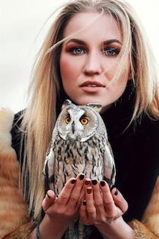 Hermosa mujer en abrigo de piel con un búho en su brazo