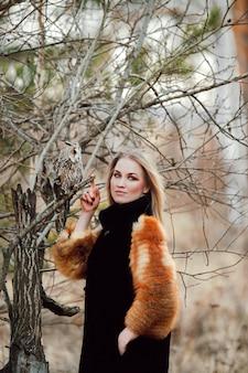 Hermosa mujer en un abrigo de piel con una lechuza en el brazo