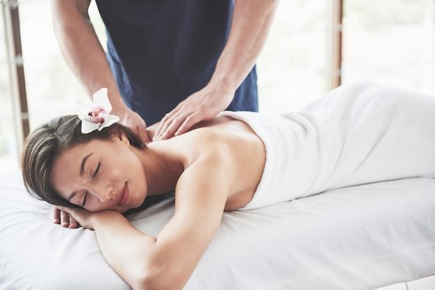 Hermosa mujer acostada en la camilla de masaje en spa.