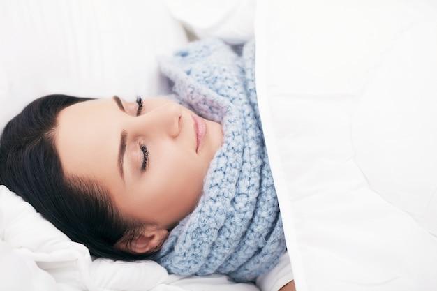Hermosa mujer acostada y dormir en la cama nevada
