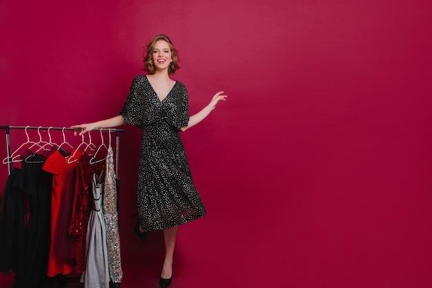 Hermosa mujer adicta a las compras bailando cerca de perchas de ropa