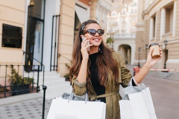 Hermosa mujer adicta a las compras con maquillaje desnudo hablando por teléfono y bebiendo café con leche en fin de semana