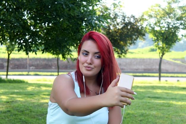 Hermosa mujer adolescente con pelo rojo tomando autorretrato