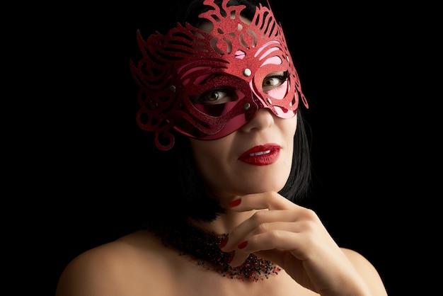 Hermosa mujer adulta de apariencia caucásica con cabello negro con una máscara de carnaval roja brillante