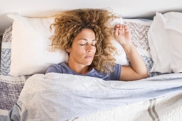 Hermosa mujer adulta caucásica dormir y relajarse en casa en la cama