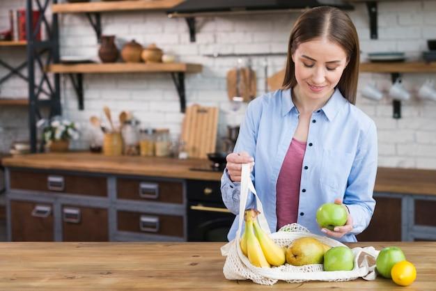 Hermosa mujer adulta comprobando frutas orgánicas
