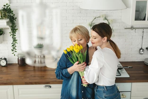 Hermosa mujer adulta está dando flores a su madre madura. dia de la mujer
