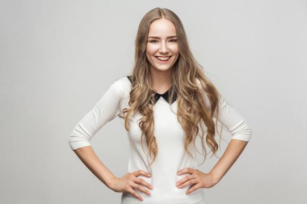 Hermosa mujer adulta joven, cogidos de la mano en el cinturón, mirando a cámara y sonriendo con dientes. tiro del estudio. aislado sobre fondo gris