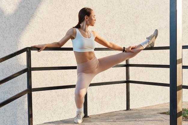 Hermosa mujer adulta joven con cuerpo perfecto, estirando las piernas al aire libre