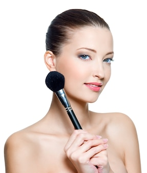 Hermosa mujer adulta joven sostiene el pincel de maquillaje para aplicar colorete o polvo aislado en blanco