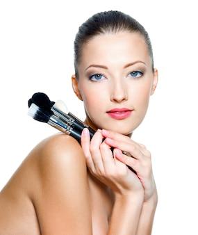 Hermosa mujer adulta joven sostiene los pinceles de maquillaje cerca de la cara atractiva aislada en blanco