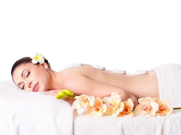 Hermosa mujer adulta relajante en el salón de spa con piedras calientes en la espalda