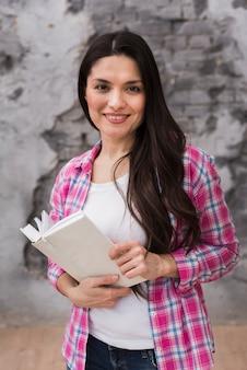 Hermosa mujer adulta sosteniendo un libro