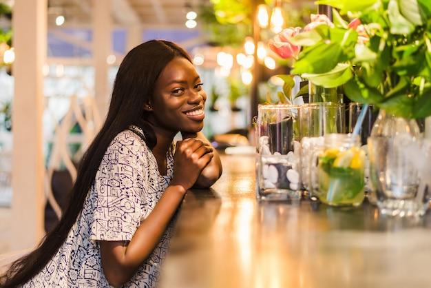 Hermosa mujer africana bebiendo limonada sentado en la cafetería.