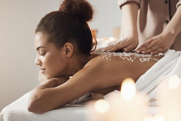 Hermosa mujer africana descansando disfrutando de masaje de salud spa con sal marina.