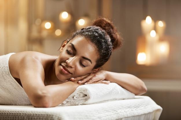 Hermosa mujer africana descansando relajante en balneario con los ojos cerrados.