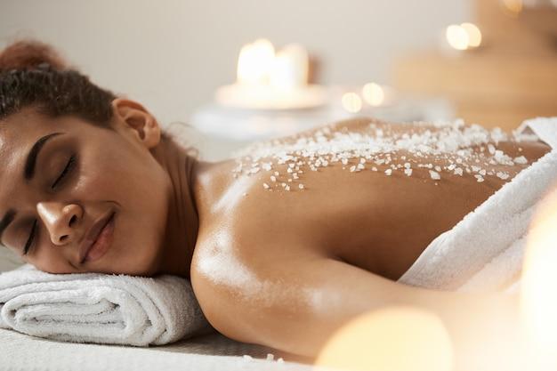 Hermosa mujer africana descansando relajante con sal de mar en la espalda en el salón de spa.