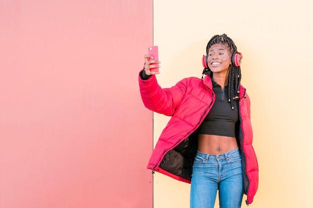 Hermosa mujer africana escuchando música con auriculares haciendo retrato selfie con smartphone
