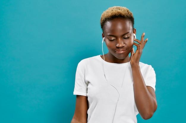 Hermosa mujer africana escuchando música con auriculares.