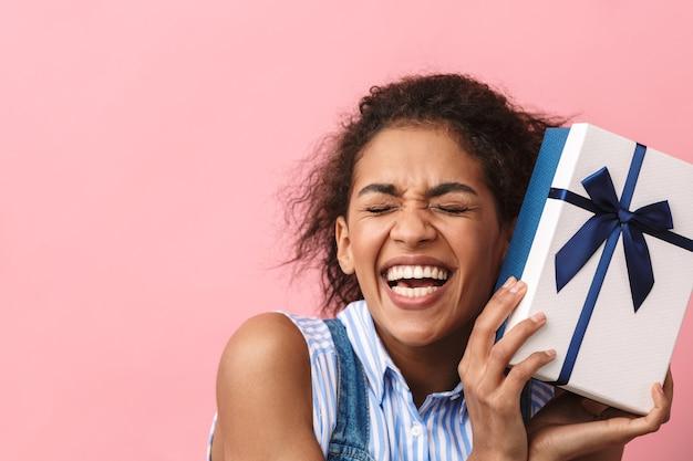 Hermosa mujer africana joven emocionada con caja de regalo sobre rosa