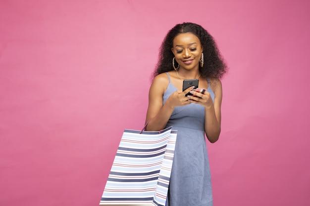 Hermosa mujer africana publicando en las redes sociales usando su teléfono inteligente sobre su juerga de compras