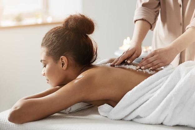 Hermosa mujer africana relajante disfrutando de masaje de salud spa con sal marina.