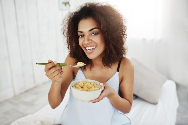 Hermosa mujer africana en ropa de dormir sonriendo comiendo copos con leche en casa por la mañana.