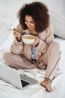 Hermosa mujer africana en ropa de dormir sonriendo mirando portátil comiendo copos con leche sentado en la cama.