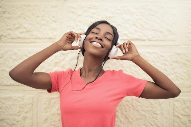 Hermosa mujer afro escuchando musica
