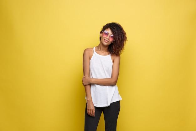 Hermosa mujer afroamericana atractiva con gafas de moda publicar sobre fondo de estudio amarillo. espacio de la copia.