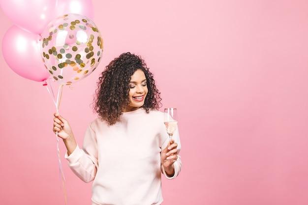 Hermosa mujer afroamericana con camiseta rosa con coloridos globos de fiesta