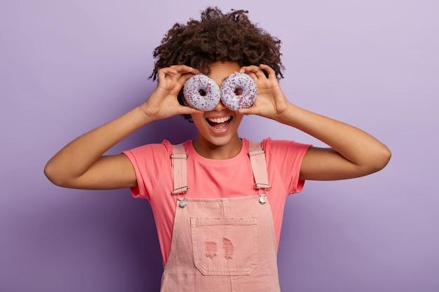 Hermosa mujer afroamericana divertida mantiene dulces donuts púrpuras en los ojos, se divierte en el interior con un delicioso postre, viste ropa rosa, aislada sobre fondo violeta. dieta, comida chatarra, concepto de pérdida de peso
