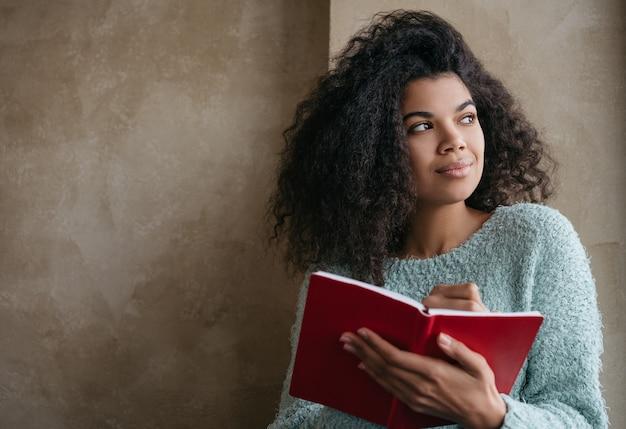 Hermosa mujer afroamericana con libro rojo, mirando por la ventana