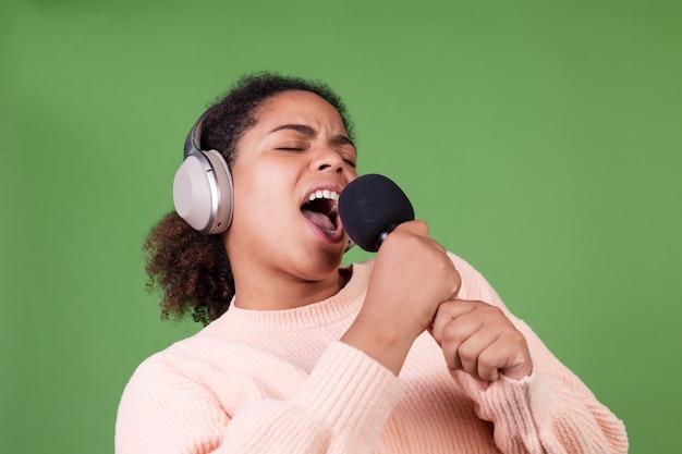 Hermosa mujer afroamericana en pared verde con auriculares inalámbricos y micrófono cantando canciones en karaoke