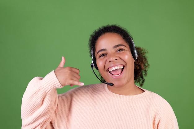 Hermosa mujer afroamericana en la pared verde trabajador del centro de llamadas del gerente feliz adorable sonriente dando la bienvenida a todas las llamadas