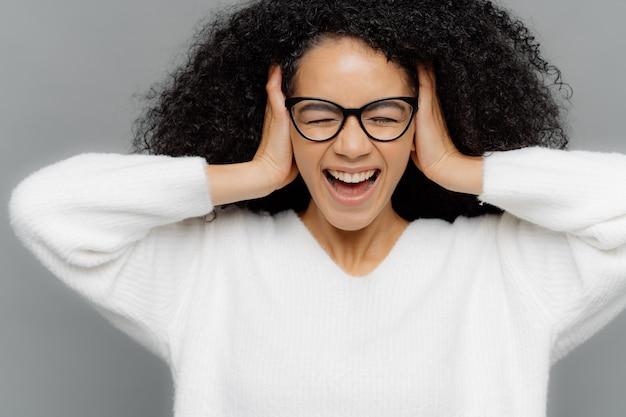 Hermosa mujer afroamericana de piel oscura estresante tiene dolor de cabeza, mantiene ambas manos sobre las orejas