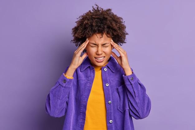 Hermosa mujer afroamericana de piel oscura toca las sienes tiene un dolor de cabeza insoportable sufre de migraña vestida con una chaqueta de terciopelo de moda.