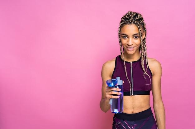Hermosa mujer afroamericana con retrato de coletas en la pared de color haciendo ejercicios deportivos
