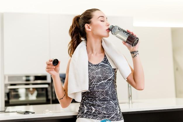 Hermosa mujer agua potable después del entrenamiento deportivo en casa