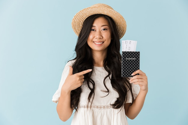 Hermosa mujer aislada sobre pared azul con pasaporte con billetes apuntando