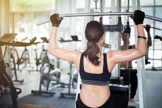 Hermosa mujer de ajuste muscular ejercicio músculos de la construcción y mujer de gimnasio haciendo ejercicios en la gy