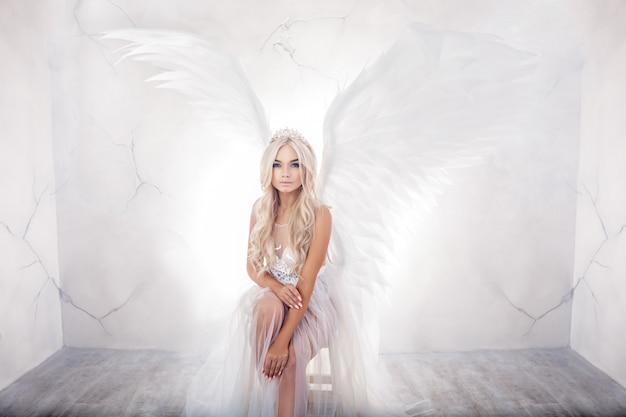 Hermosa mujer con alas blancas sobre fondo blanco