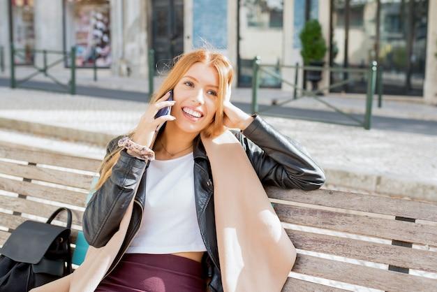 Hermosa mujer alegre disfrutando de una conversación telefónica