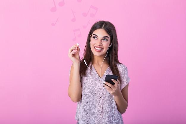 Hermosa mujer alegre escuchando música con auriculares en el teléfono móvil.