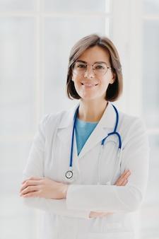Hermosa mujer alegre médico lleva bata blanca, gafas y fonendoscopio, mantiene las manos cruzadas