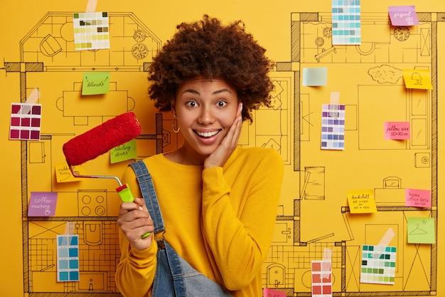 Hermosa mujer alegre de piel oscura ocupada con la redecoración de la casa, se muda a un nuevo apartamento, sostiene el rodillo de pintura, descansa después de pintar las paredes, usa un suéter amarillo y un mono, se para sobre el boceto de diseño