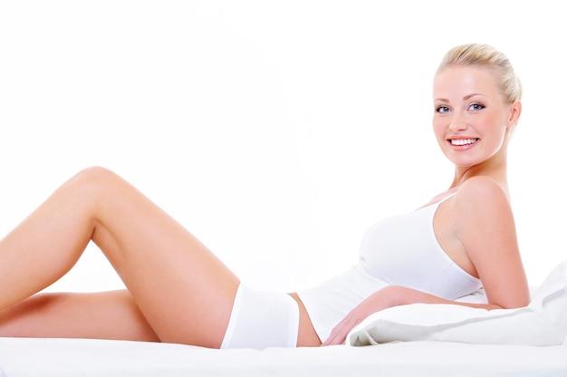 Hermosa mujer alegre con piernas perfectas en lencería blanca acostada en la cama