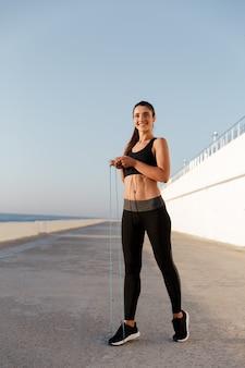 Hermosa mujer alegre con saltar la cuerda entrenamiento aislado