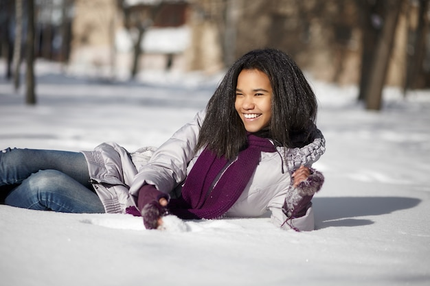 Hermosa mujer americana negra sonriente tumbado en la nieve al aire libre