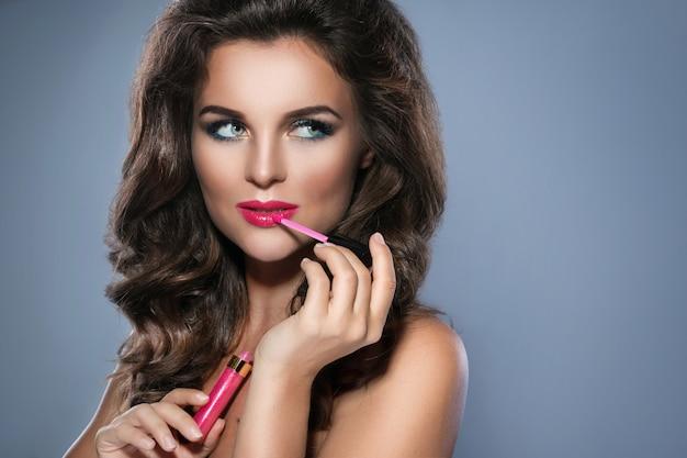 Hermosa mujer aplicando brillo labial